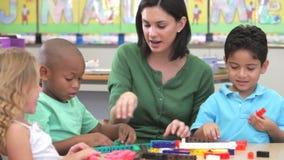 老师坐与使用建筑成套工具的小组孩子 股票视频