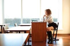 老师坐在书桌在教室并且等待学生 免版税图库摄影