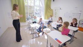 老师女性与小逗人喜爱的儿童学童互动在书桌在教育教训期间在教室在学校 股票视频
