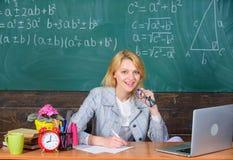 老师妇女坐桌黑板背景 优秀传染性和人际的技能 组织类和 免版税库存图片