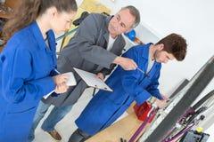 老师工程师和学生由电子电动机控制盘区 库存图片