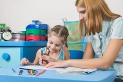 老师帮助一个五年女孩以统治者画 免版税库存照片