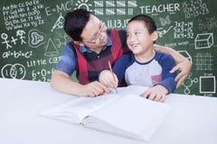 老师帮助一个小孩学会 免版税库存照片