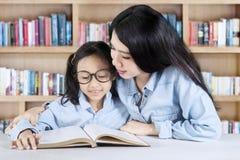 老师帮助她的学生读课本 免版税库存照片
