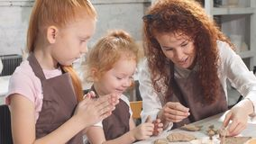 老师帮助孩子删去有小铲的黏土小雕象或刀子、展示和Explanes,孩子设法切开自己 股票录像