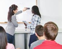 老师帮助有算术惯例的一名学生 库存照片