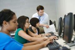 老师帮助的学生在计算机实验室 免版税库存照片