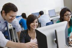老师帮助的学生在计算机实验室 库存图片