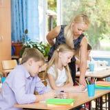 老师帮助的学生解释如何解决任务 免版税图库摄影