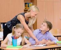 老师帮助的学生解释如何解决任务 免版税库存照片