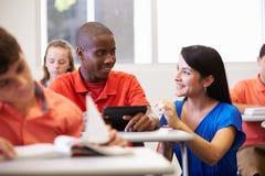 老师帮助的男性高中学生在教室 免版税库存图片