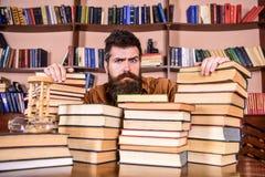 老师或学生有胡子的坐在桌上与书, defocused 严肃的面孔的人在堆书之间,当时 免版税图库摄影