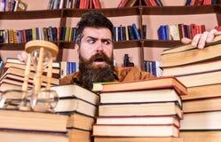 老师或学生有胡子的坐在桌上与书, defocused 珍藏书籍者概念 之间迷茫的面孔的人 免版税库存照片