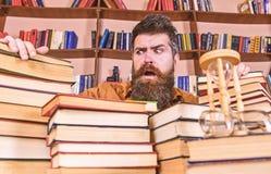 老师或学生有胡子的坐在桌上与书, defocused 珍藏书籍者概念 之间迷茫的面孔的人 图库摄影