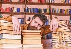 老师或学生有胡子的睡着在书, defocused 睡觉面孔的人放置在堆书之间,秋天 免版税库存照片