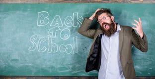 老师或教育家站立有题字的近的黑板回到学校 老师不快乐呼喊歇斯底里面孔 库存照片