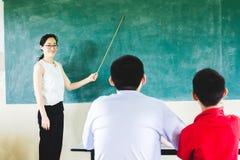 老师教学在教室有黑板背景 库存照片
