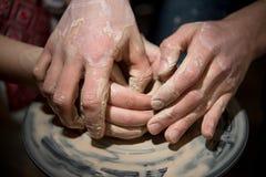 老师教孩子如何铸造一个陶瓷水罐 免版税库存图片