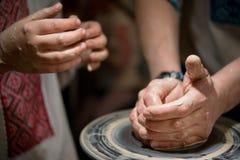 老师教孩子如何铸造一个陶瓷水罐 库存照片