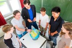 老师教的学生地理教训在学校 免版税库存照片