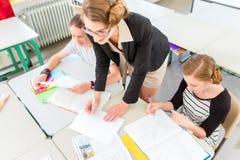 老师教的学生地理教训在学校 免版税库存图片