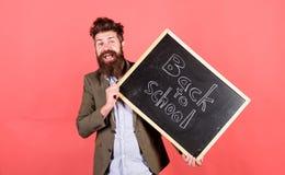 老师有胡子的人拿着有题字的黑板回到学校红色背景 教的紧张职业 库存照片