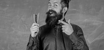 老师有胡子的人有订书机黑板背景 为学校季节购买文具做准备 人微笑的举行 图库摄影