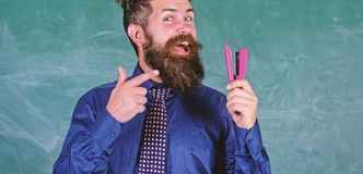 老师有胡子的人有订书机黑板背景 为学校季节购买文具做准备 人微笑的举行 库存照片