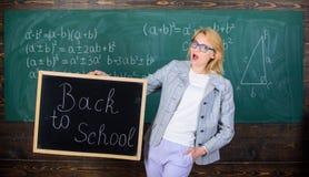 老师欢迎新的学年 新的学校季节初期  妇女老师正式衣服拿着黑板题字 免版税库存照片