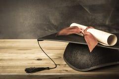 老师的书桌-毕业盖帽&文凭 免版税库存照片