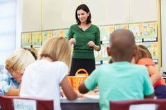 老师谈话与基本的学生在教室 库存图片