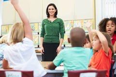 老师谈话与基本的学生在教室 库存照片