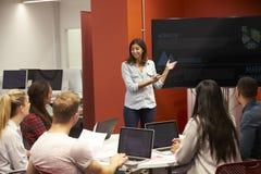 老师谈话与学院类的学生 免版税库存图片