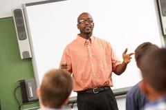 老师谈话与站立在Whiteboard前面的类 库存照片