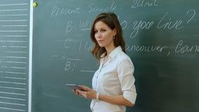 老师谈话与类在黑板附近 免版税库存照片
