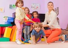 老师,孩子在幼儿园打与箍的比赛 免版税库存照片