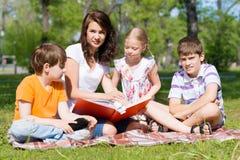 老师读一本书给孩子在夏天公园 免版税库存照片