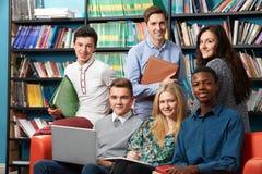 老师画象有学生的在图书馆里 免版税库存照片