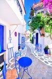 老希腊镇、狭窄的街道、白色墙壁、蓝色家具和美丽的九重葛 免版税库存照片