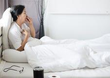 老年人亚裔妇女咳嗽和坐她的床,女性喉咙痛,健康的概念 图库摄影