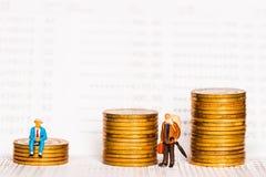 老年人形象坐堆银币在银行存款簿 免版税图库摄影