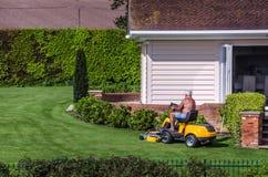 老年人骑马割草机在庭院里 库存图片