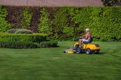 老年人骑马割草机在庭院里 免版税库存图片