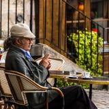 老年迈的人坐餐馆的大阳台用咖啡a 免版税库存照片