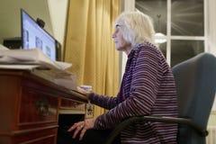 老年长资深人学会计算机的和网上互联网技能当心金钱欺骗诈欺垃圾短信 免版税图库摄影