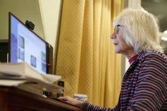 老年长资深人学会计算机的和网上互联网技能当心金钱欺骗诈欺垃圾短信 免版税库存图片