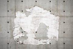 老广告牌和灰色墙壁有被撕毁的海报的 图库摄影
