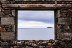 从老废墟的一个石窗口的海视图在海洋附近的 免版税库存图片