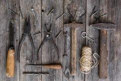 老建筑用工具加工锤子,钳子,螺丝刀,在暗色年迈的木板的凿子谎言与传神纹理的 免版税库存图片