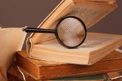 老开放书和放大镜 免版税库存图片